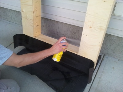Applying spray to the corners of the window frame